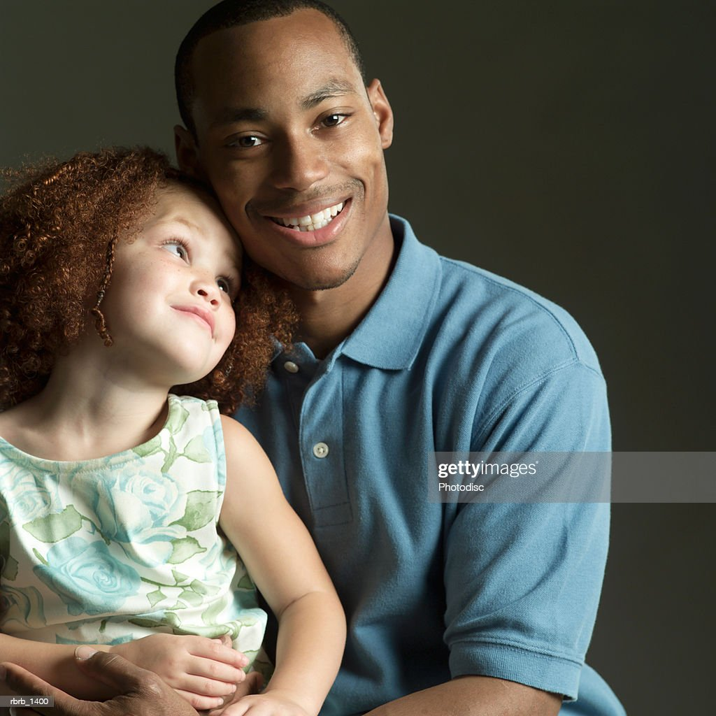 studio portrait of an african american father smiling while holding his young daughter : Stockfoto