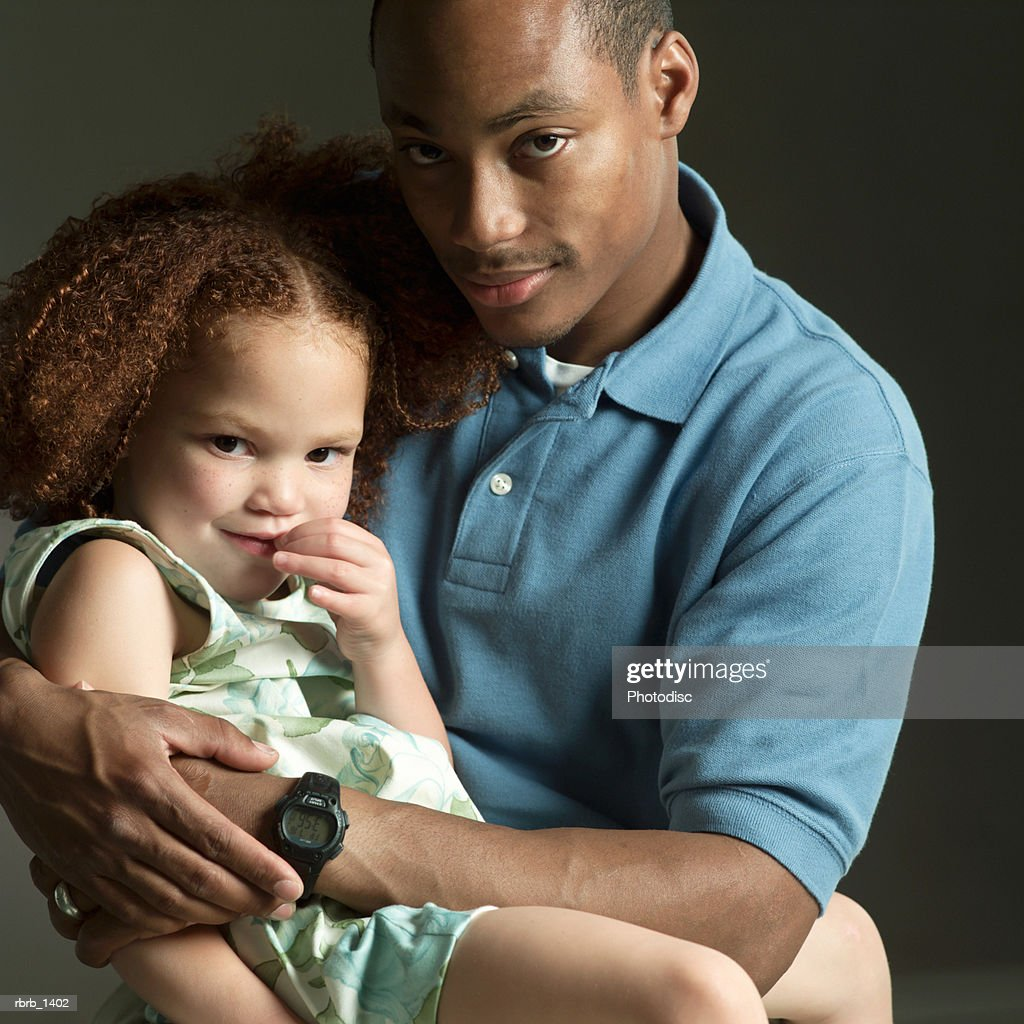 studio portrait of an african american father smiling while holding his young daughter : Stock Photo