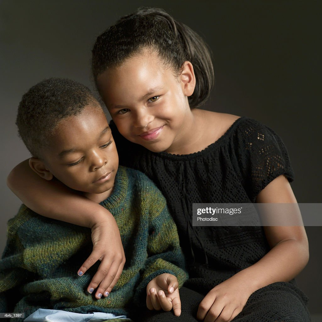studio portrait of an african american girl putting her arm around her little brother : Stockfoto