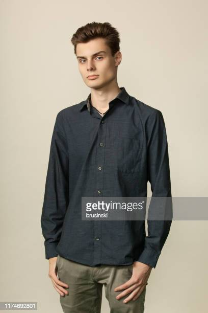 studio portrait of an attractive 18 year old man in a gray shirt and khaki pants on a beige background - khaki trousers stock pictures, royalty-free photos & images