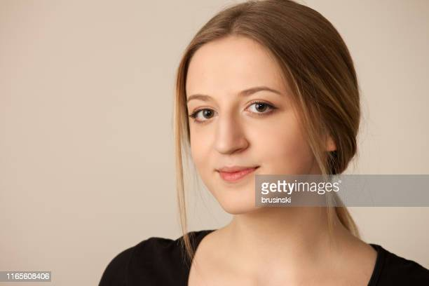 studio portrait of an attractive 18 year old woman on a beige background - three quarter front view stock pictures, royalty-free photos & images
