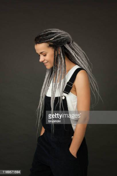 studio portrait of an attractive 27 year old woman with dreadlocks on a black background - dreadlocks stock pictures, royalty-free photos & images