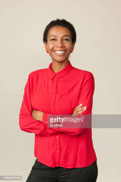 studio portrait of an attractive 30 year old woman in a red shirt on a beige background - red shirt stock pictures, royalty-free photos & images