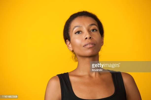 retrato do estúdio de uma mulher atrativa dos anos de idade 30 em uma parte superior de tanque preta em um fundo amarelo - fundo amarelo - fotografias e filmes do acervo