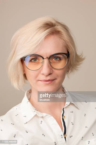 studio portrait of an attractive 40 year old blonde woman with glasses on a beige background - beige background stock pictures, royalty-free photos & images
