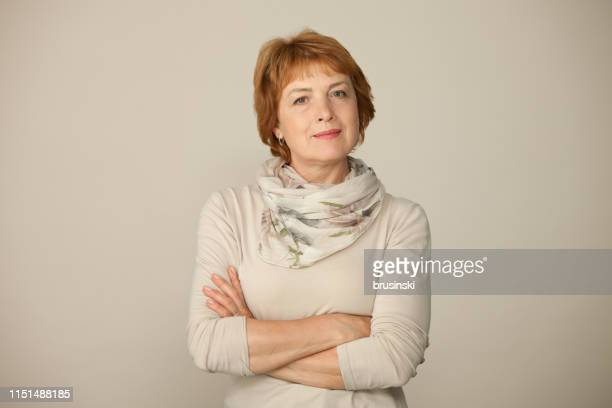 studio portrait of an attractive 60 year old woman on a beige background - 63 year old female stock pictures, royalty-free photos & images