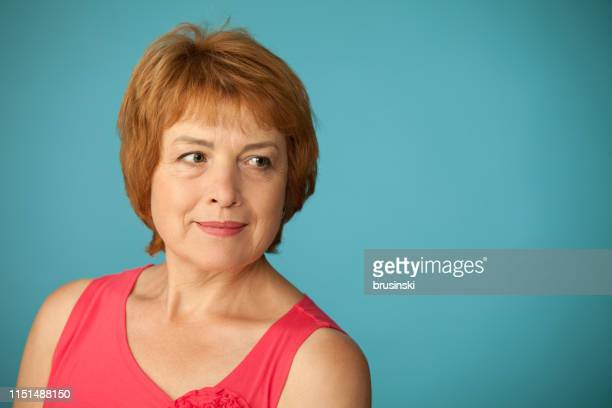 studio portrait of an attractive 60 year old woman on a blue background - 63 year old female stock pictures, royalty-free photos & images