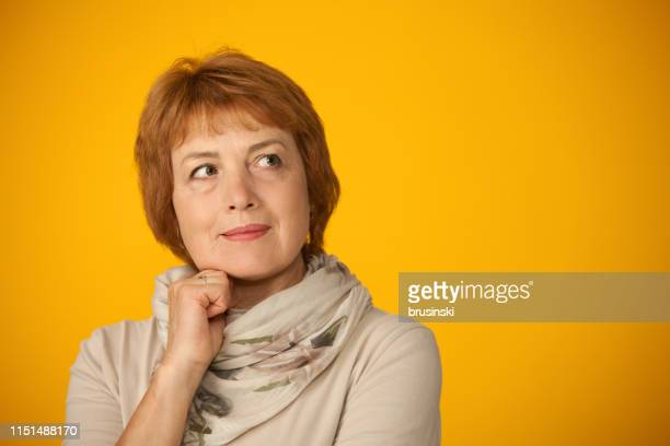 studio portrait of an attractive 60 year old woman on yellow background - 63 year old female stock pictures, royalty-free photos & images