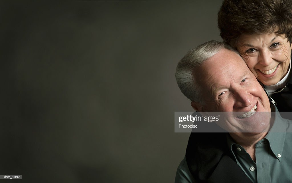 studio portrait of an elderly caucasian couple as the woman hugs and smiles with the man : Stockfoto
