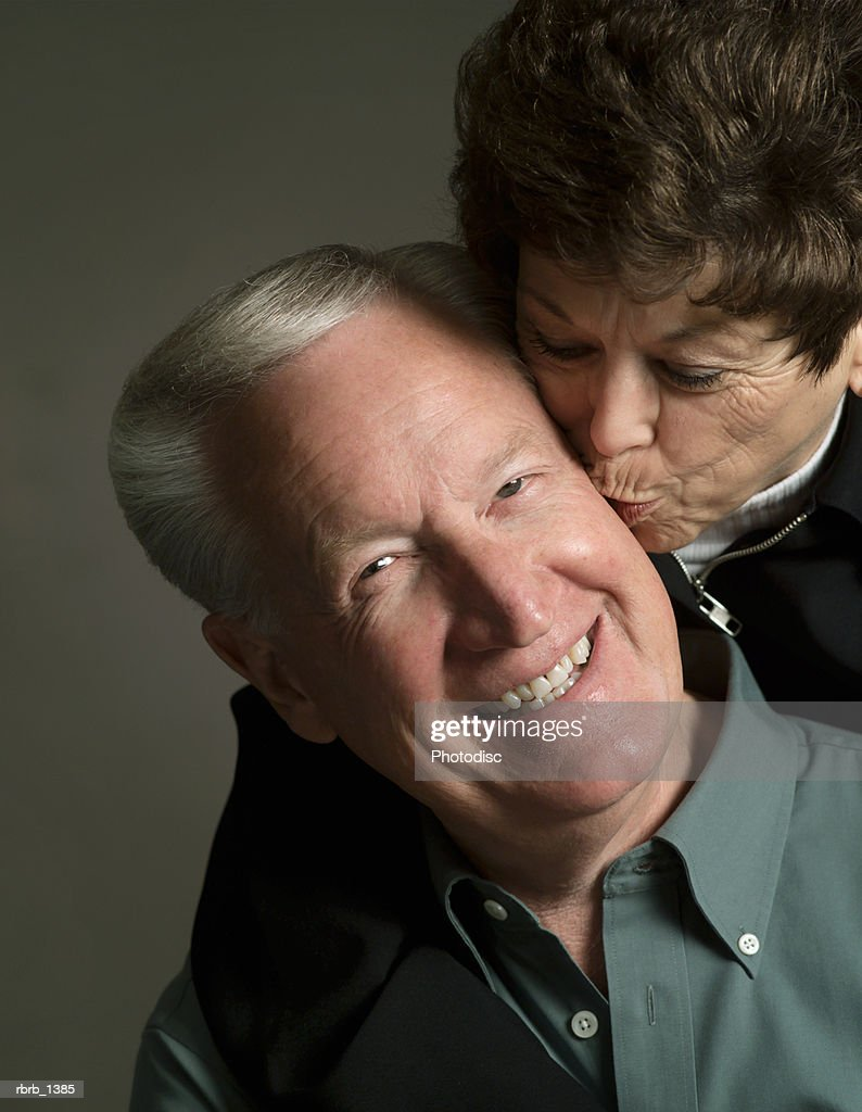 studio portrait of an elderly caucasian couple as the woman kisses the cheek of the man : Stock-Foto