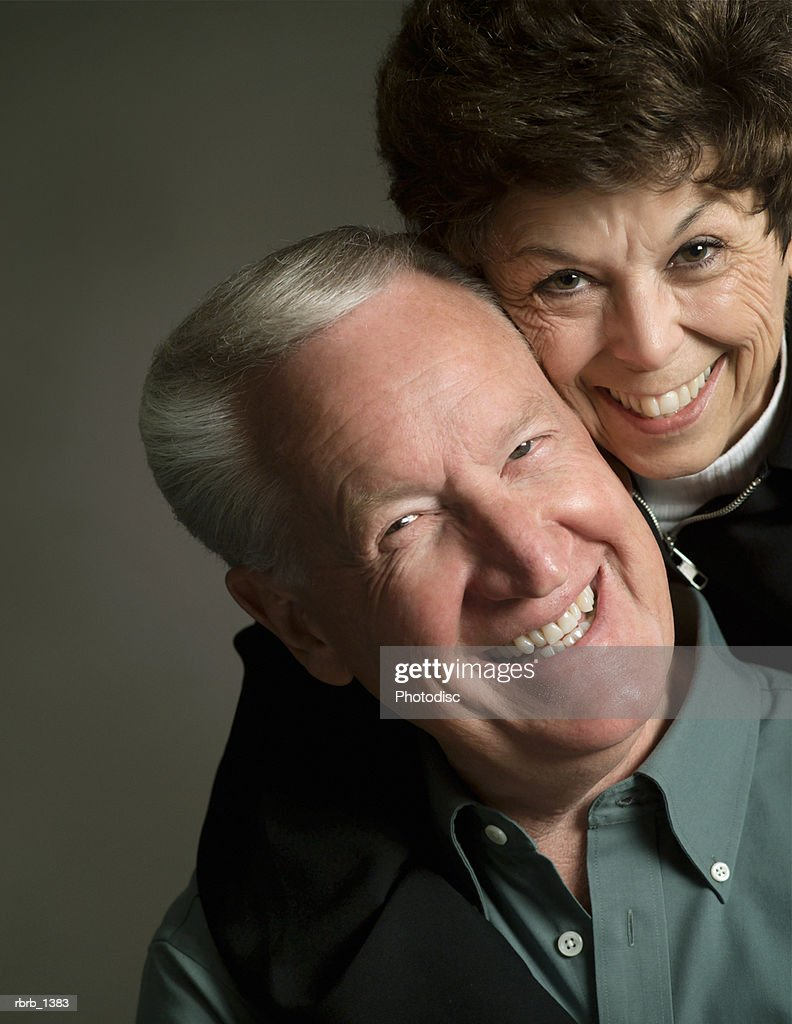 studio portrait of an elderly caucasian couple as the woman laughs and smiles with the man : Stockfoto