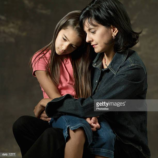 studio portrait of an ethnic mother as she holds her young daughter on her lap and hugs her lovingly