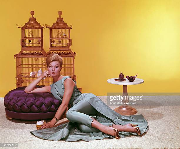 Studio portrait of an unidentified model as she as she sits on the floor a glass of beer at her side and one arm on a low purple stool in front of...