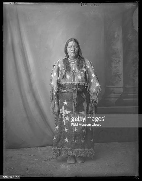 Studio portrait of an unidentified Native American Arapaho older woman, possibly partially blind, wearing a hair ornament, and a painted and fringed...