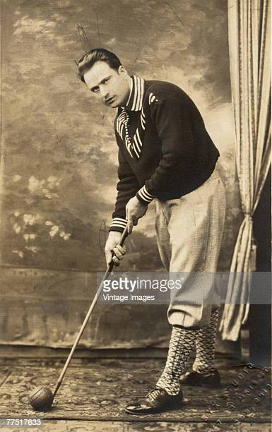 Studio portrait of an unidentified, well-dressed indoor golfer, who poses with a club and ball at the ready, Akron, Ohio, late 1800s or early 1900s.