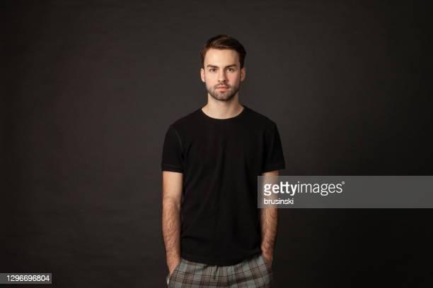 ritratto in studio di attraente uomo barbuto di 20 anni - top nero foto e immagini stock