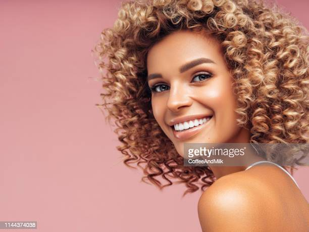 studio portrait of attractive young girl over pink wall - cabelo encaracolado imagens e fotografias de stock