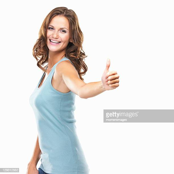 Studio portrait of attractive young woman with thumbs up