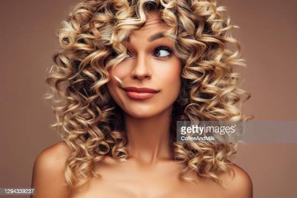 studio portrait of attractive young woman with voluminous curly hairstyle - cabelo encaracolado imagens e fotografias de stock