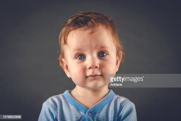 studio portrait of baby boy aged 9 months on grey-blue background - one baby boy only stock pictures, royalty-free photos & images