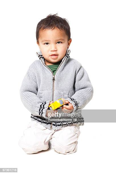 Studio portrait of baby boy (18-23 months) playing with toy car