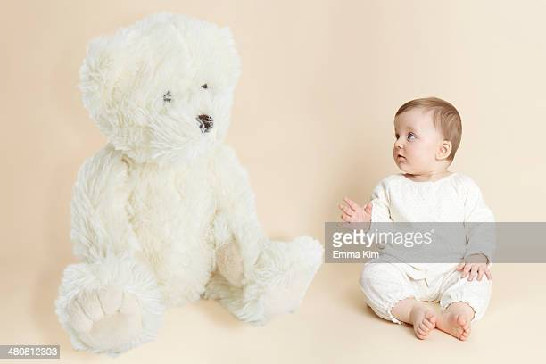 Studio portrait of baby girl next to giant teddy bear