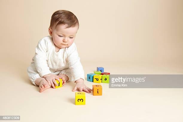Studio portrait of baby girl playing with alphabet blocks