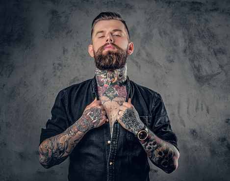Studio portrait of bearded hipster man with tattoos. 932704186