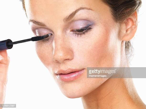 Studio portrait of beautiful brunette applying mascara