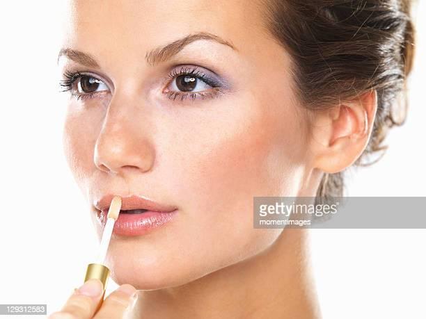 Studio portrait of beautiful woman applying lip gloss