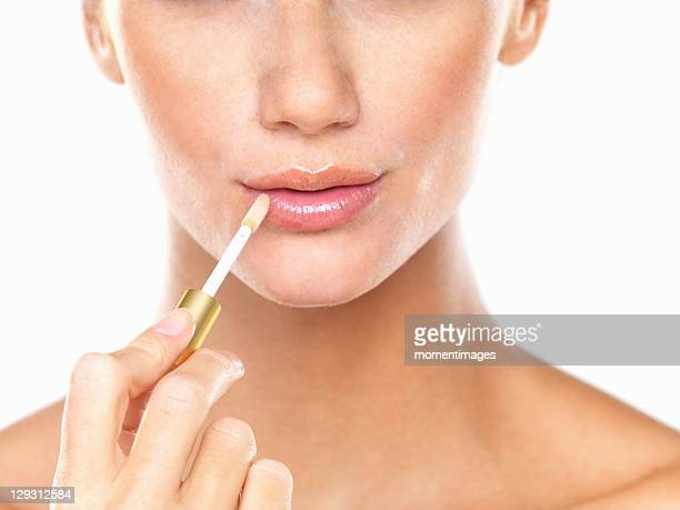 Studio portrait of beautiful woman applying lip gloss