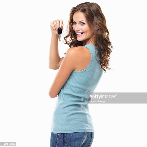 Studio portrait of beautiful woman turning around and holding car keys