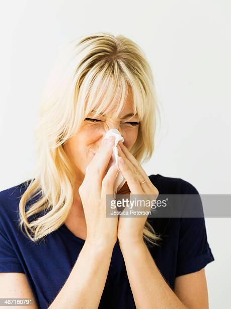 Studio portrait of blonde woman blowing nose