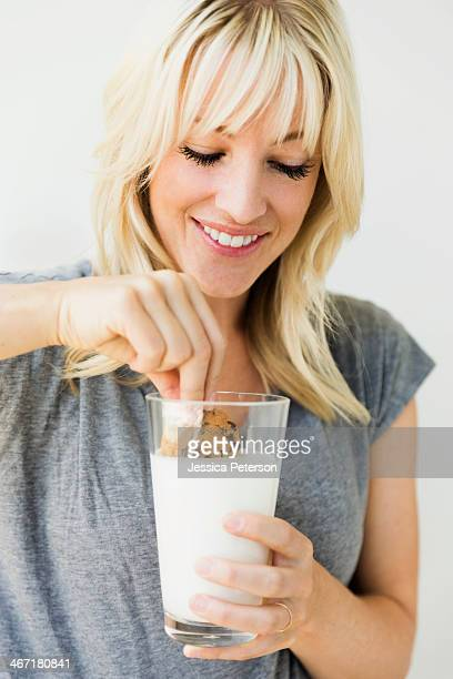 studio portrait of blonde woman dipping cookie in milk - dipping stock photos and pictures
