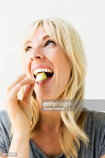 Studio portrait of blonde woman eating bubble gum