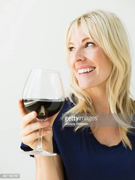 studio portrait of blonde woman with wineglass - mid adult women stock pictures, royalty-free photos & images