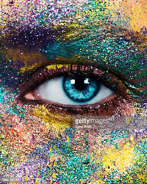 studio portrait of blue eyed young woman with glittery multi coloured powder on face, close up of eye - luce vivida foto e immagini stock