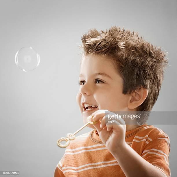 Studio portrait of boy (8-9) blowing bubbles