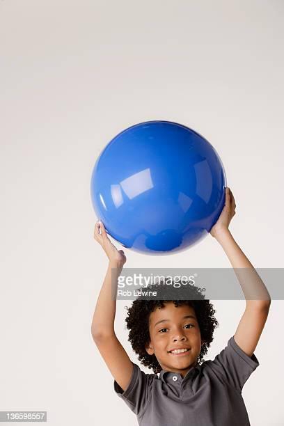 studio portrait of boy (8-9) holding blue ball - un seul petit garçon photos et images de collection