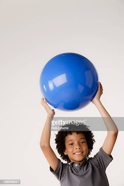 Studio portrait of boy (8-9) holding blue ball