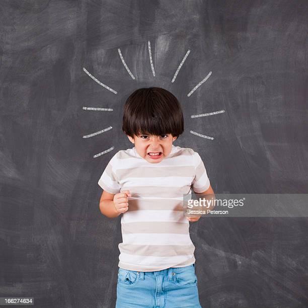 Studio portrait of boy (6-7) in front of blackboard
