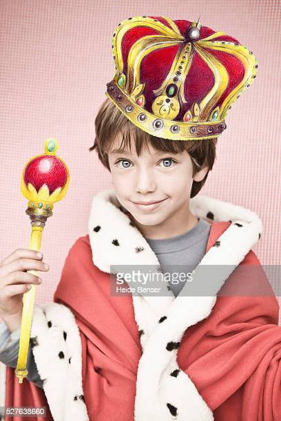 Studio portrait of boy (7-9) in king costume
