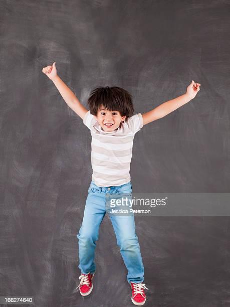 Studio portrait of boy (6-7) jumping in front of blackboard