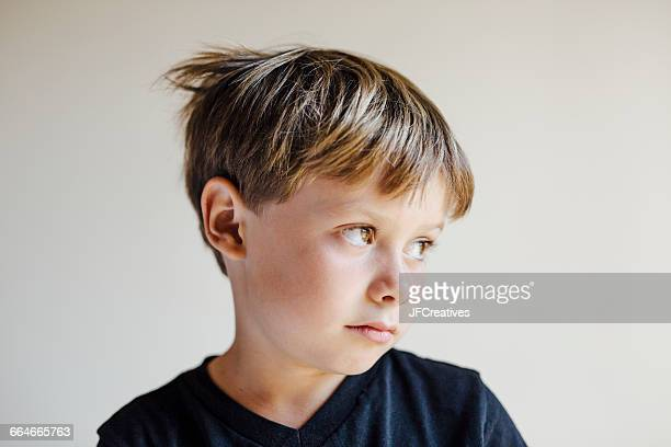 studio portrait of boy looking away - verlegen stockfoto's en -beelden