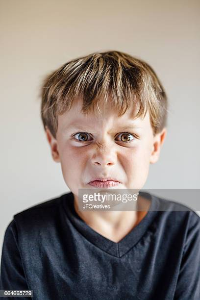 studio portrait of boy pulling wrinkled face - alleen jongens stockfoto's en -beelden
