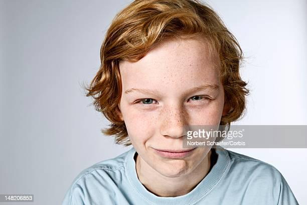 studio portrait of boy (10-12) squinting - 12 13 jaar stockfoto's en -beelden