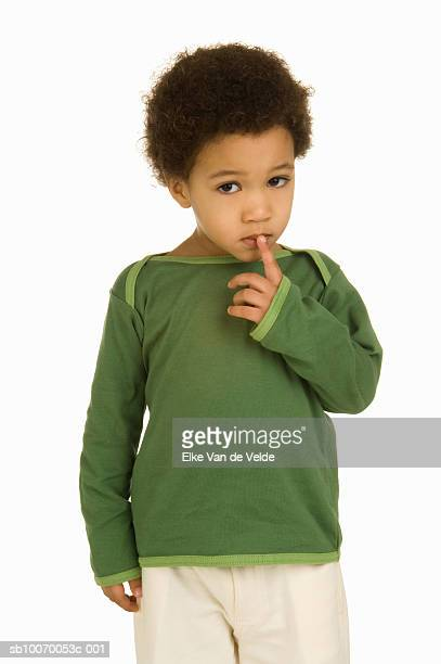 Studio portrait of boy (2-3) with finger on mouth