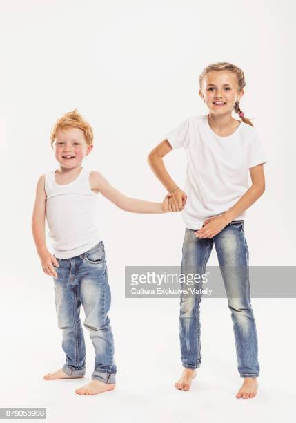 Studio portrait of brother and sister, holding hands