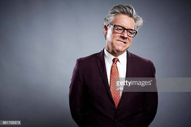 studio portrait of businessman biting his lip - biting lip stock pictures, royalty-free photos & images