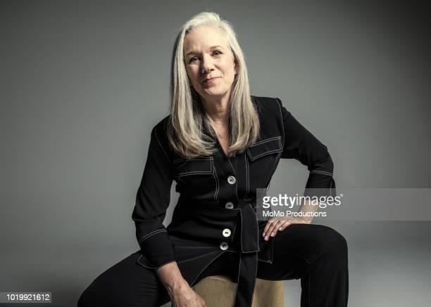 studio portrait of businesswoman - hocker stock-fotos und bilder